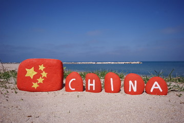 China flag and name on pebbles with sea background