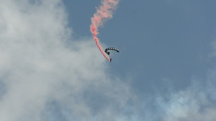 Skydivers with a trail of smoke behind
