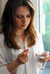 Beautiful woman holding a pill and a glass of water