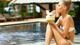 Girl sitting at the edge of pool and drinking from coconut
