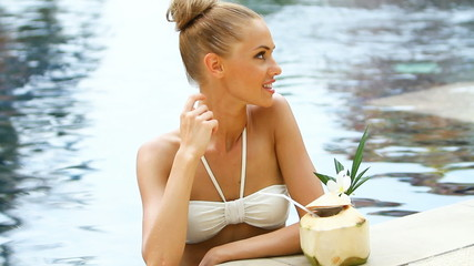 Woman standing in swimming pool and drink from coconut