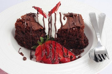 Chocolate brownies with strawberries and cream