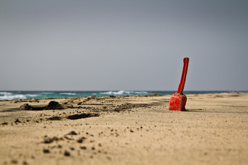 A single red shovel on a secluded sandy beach.