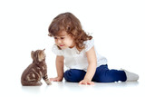 Funny child sitting on floor. Scottish kitten looking at girl.