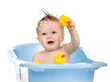 charming baby having bath in blue tub and playing with soap bubb