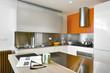 cucina moderna con alzata di acciaio e muro arancione