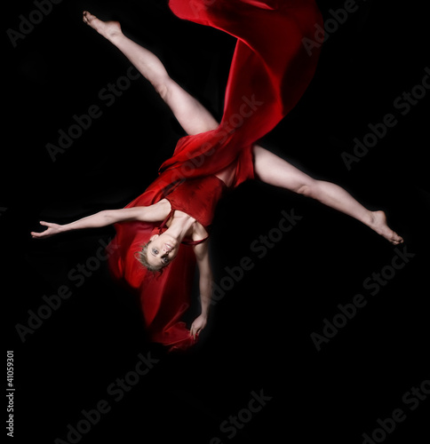 Young woman gymnast on black background