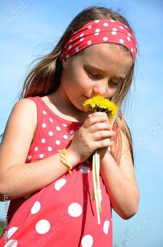 Mädchen riecht an einem kleinen Blumenstrauß