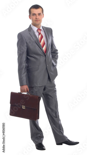 Portrait of a happy young business man holding suitcase