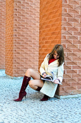 Smiling female sits and reads a book at the wall