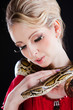 attractive blond woman with python on black