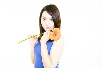 ガーベラの花を持つ美しい女性