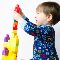 Baby boy builds a tower with colorful plastic blocks