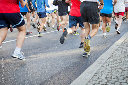 People running in city marathon on street