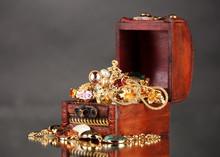 Coffre en bois pleine de bijoux en or sur fond gris