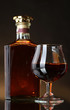 Glass of brandy and bottle on brown background