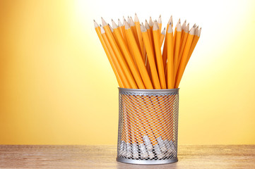 lead pencils in metal cup on wooden table on yellow background