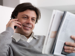 Happy man buying from catalogue with telephone