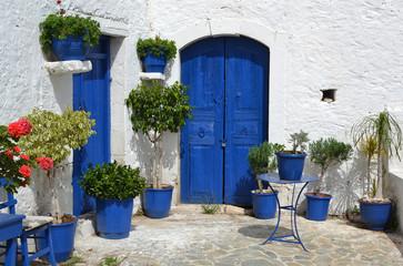 Typical greek courtyard with blue flower pots in Piskopiano.