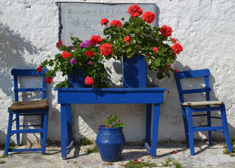 Typical greek courtyard with blue flower pots in Piskopiano.