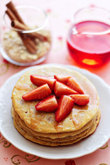 A stack of pancakes with fresh strawberries and syrup