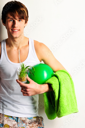 Healthy man holding ball and towel. Standing against wall.