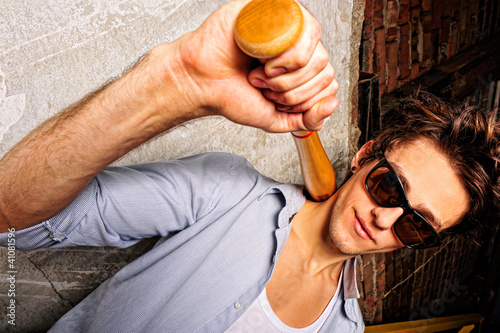 Portrait of young guy with bat leaning on the wall