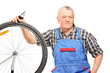Middle aged male holding pliers and repairing bicycle wheel