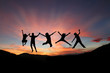 silhouette of teens jumping in front of mountain range