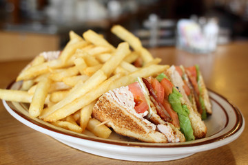 Delicious club sandwich with french fries at a diner.