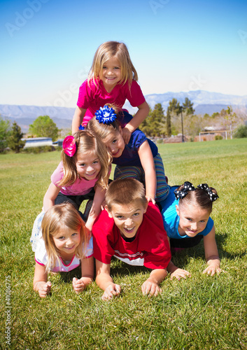 Cute Kids Building a Human Pyramid outdoors