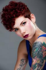 Cute young tattooed female in bule top