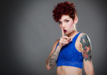 Pretty young female with tattoos and finger to mouth