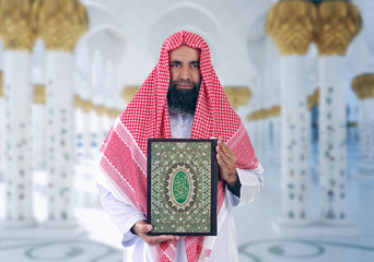 Arabian Islamic Sheikh presenting holy book of islam Qur'an