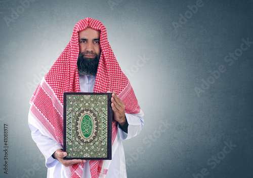 "Islamic Arabian Sheikh presenting the holy book "" Quran """