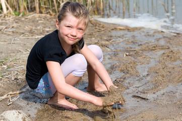 Mädchen spielt mit Wasser am Strand