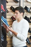 Young man at choosing shoe in clothes store