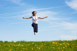 Fototapety smiling young girl jumping against blue sky