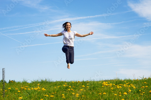 smiling young girl jumping against blue sky