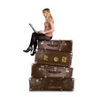 Beautiful blond girl sitting on suitcases and writing on laptop