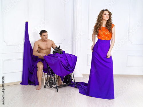 The beautiful girl with the man sew a dress