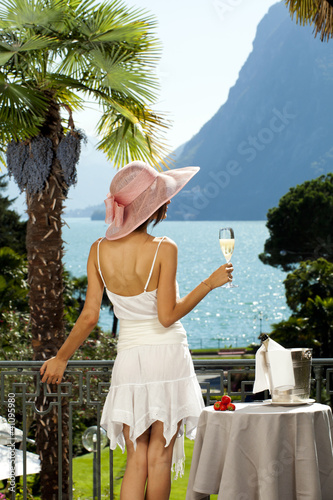 Girl drinks champagne on the terrace a prestigious hotel