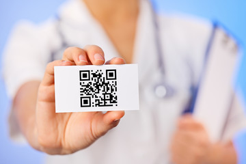 Doctor holding business card with health care QR code on blue