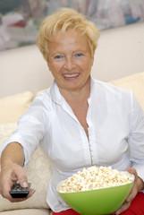 Una señora comiendo palomitas de maíz viendo televisión.