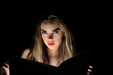 Portrait of young sexy woman reading a magic book