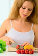 young woman, a housewife preparing dinner vegetable salad in the