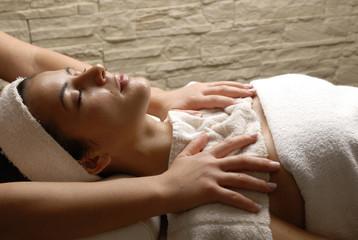 Joven mujer recibiendo un masaje en un sauna.