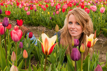 Dutch blond girl laying in field with tulips