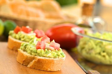 Baguettescheiben mit Avokadokrem, Tomaten und Zwiebeln
