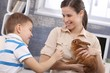 Smiling mum and little son with pet rabbit